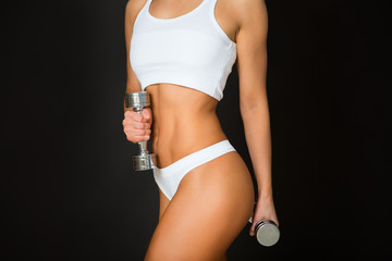 Torso of a young fit woman lifting dumbbells on black background