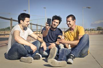 Three friends sitting on the ground