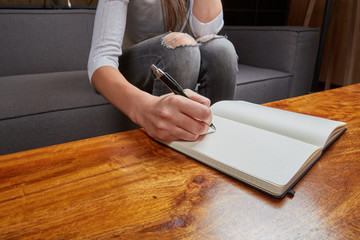 Woman writing in a book with pen