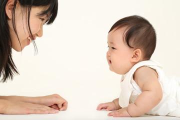 お母さんに向かいハイハイする赤ちゃん