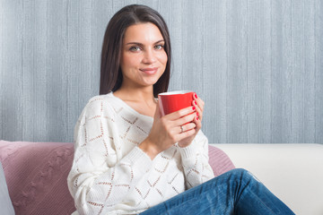 Woman  with a red mug in her hands, smiles sittings on the couch, sofa look at camera