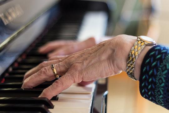 Seniorin spielt am Klavier um gelenkige Finger zu erhalten