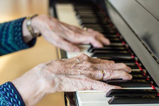Hände einer alten Frau am Klavier