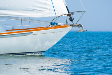 Closeup of a beautiful sailboat bow cutting through beautiful blue water under full sail on a cloudless sunny morning