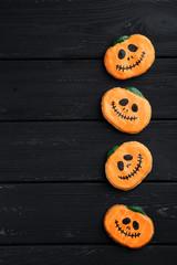 Fresh halloween gingerbread cookies on black wooden table