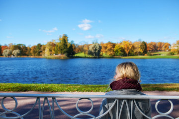girl sitting on a bench by the lake in the autumn park