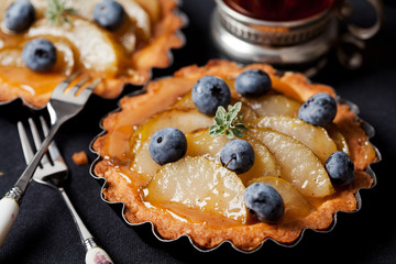 Homemade pear and blueberry tarts on black
