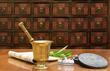 Traditional Chinese medicine pharmacy with a brass mortar and fresh herb and ancient medicine book