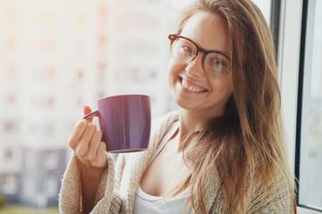 cheerful girl drinking coffee or tea in morning sunlight near wi