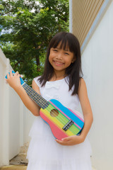 Young asian funny girl having fun and playing on small colorful ukulele guitar
