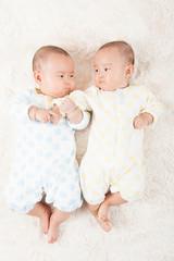 寝そべっている双子の赤ちゃん