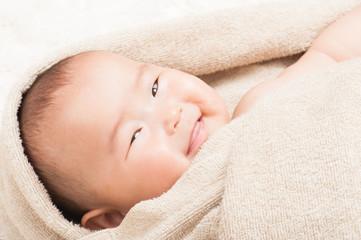 タオルの中で笑顔の赤ちゃん
