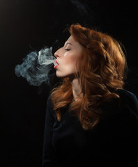Portrait of a beautiful woman who smokes on a black background.