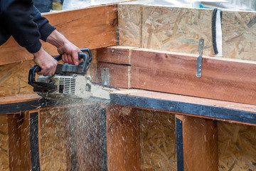 Man sawing wood with electrical saw