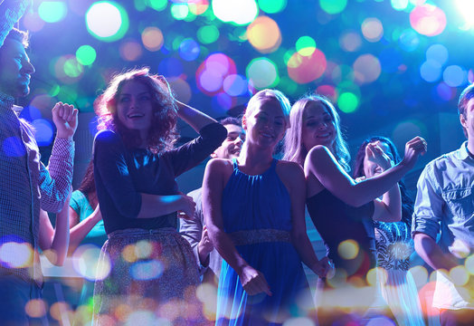 group of happy friends dancing in night club