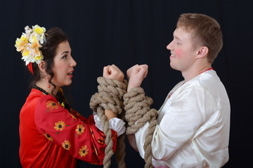 blonde and brunette tied with rope hands