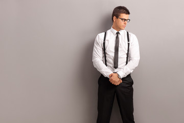 Elegant man standing against a gray wall