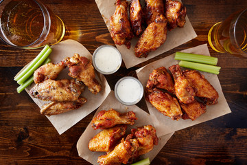 Tuinposter Buffel overhead view of four different flavored chicken wings with ranch dressing, beer, and celery sticks