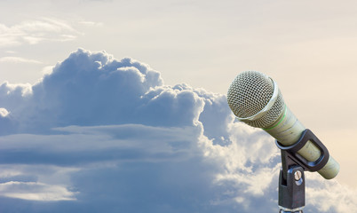 microphone on a stand with blurred gray big cloud before raining