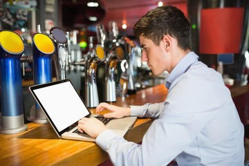 Man using laptop at bar counter