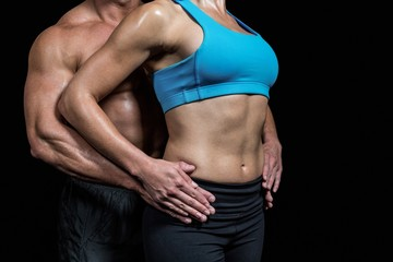 Midsection of healthy couple with hands on hip