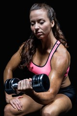 Thoughtful athlete sitting while lifting dumbbell