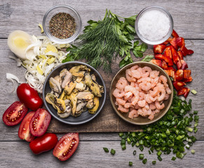 ingredients for cooking mussels shrimp on a wooden cutting board  on wooden background top view