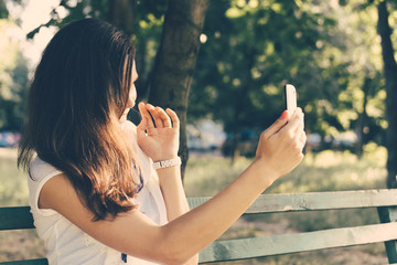 Young woman sitting on a park bench and photographed on a mobile