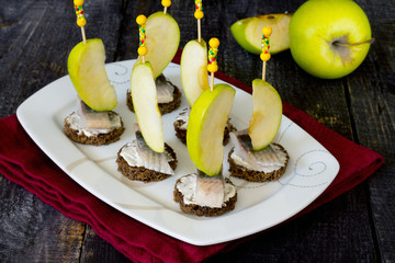 Appetizer canape with herring, apples and black bread