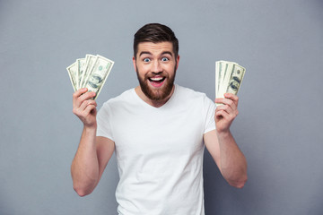 Cheerful man holding dollar bills