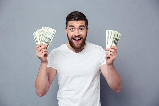 Cheerful man holding dollar bills