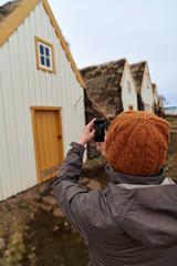Tourist taking picture of historic farmhouse