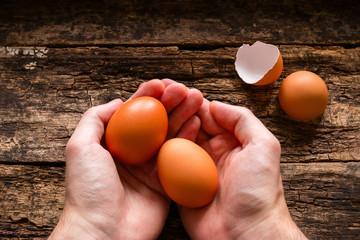 man holding eggs wood background