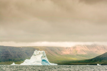 A single ice bergs sits off a green, tundra valley.