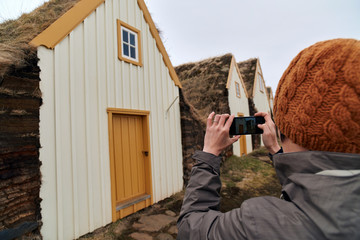 Tourist taking picture of historic farmhouse