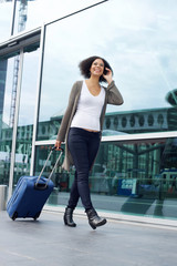 Traveling woman walking with suitcase and mobile phone