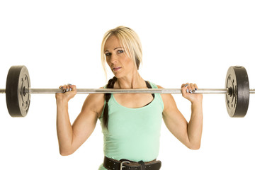 woman in green tank top and barbell by chest looking