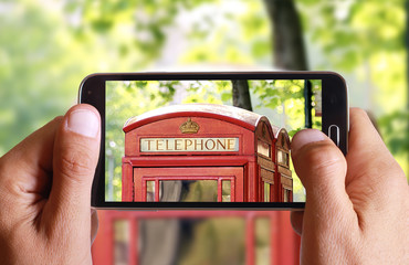 Male hand taking photo of phone cabin in London with cell, mobile phone. England holiday.