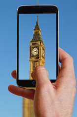 Male hand taking photo of Big Ben in London with cell, mobile phone. England holiday.