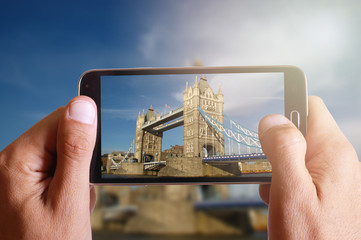 Male hand taking photo of London bridge with cell, mobile phone.