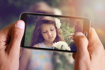Male hand taking photo of Vintage Portrait of beautiful girl with cell, mobile phone. Kids, childhood, family concept.