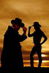 silhouette of a cowgirl side touch hat look down cowboy.