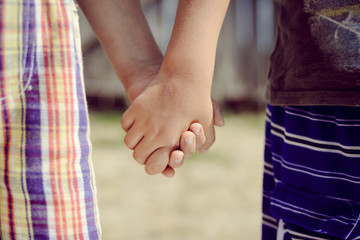 Closeup of two child's hands holding each other in countryside