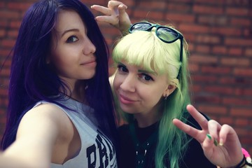 Closeup fashion lifestyle portrait of two young pretty beautiful friends with color hair making selfie
