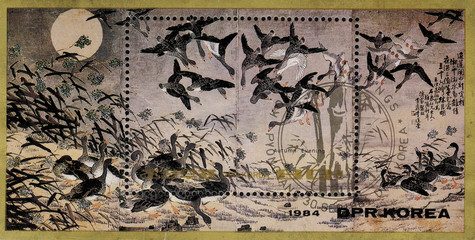 postage stamp/ DPR KOREA - CIRCA 1984: mail stamp printed in DPR Korea featuring Reproduction of autumn evening. Shown are wild geese, pond beach, sun and vegetation, circa 1984