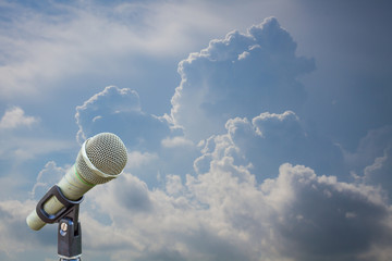 microphone on a stand with blurred dark blue stormy clouds.