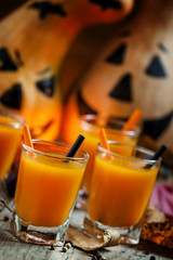 Fresh pumpkin juice on a dark Halloween background with burning
