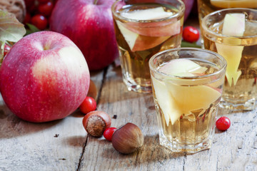 Apple juice with slices of fresh apples in the autumn background
