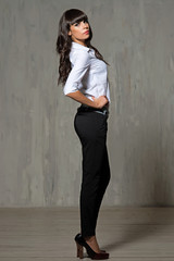 the slender woman in a shirt and trousers