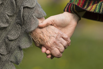 Holding hands together - old and young, close-up outdoors.
